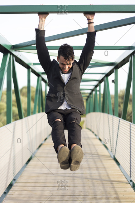 Young stylish man in suit hanging on the bridge rod