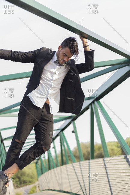 Young man in suit hanging on the bridge rod