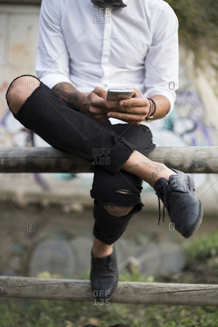 Unrecognizable stylish man using smart phone