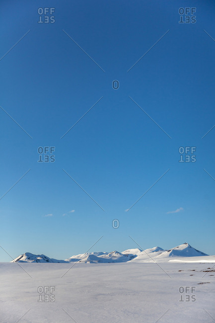 Snow covered mountains under blue sky in rural Iceland