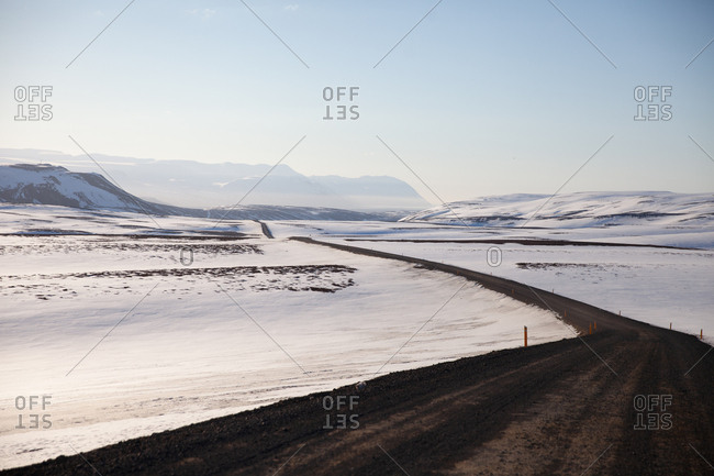 Dirt road surrounded by snow-covered fields in rural Iceland