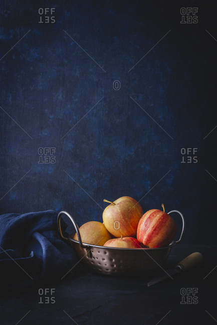 Bowl of apples with dark blue background