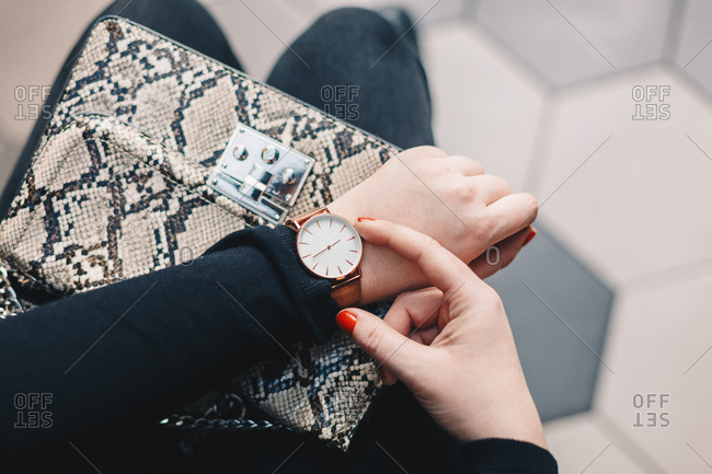 Close up detail of a female fingers fixing the time on a hand watch, with the snakeskin purse in the background.