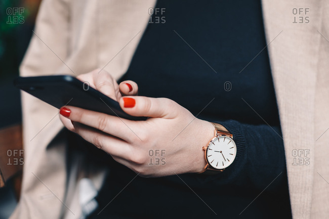 Close up detail of young female hands using a mobile phone while wearing a golden wrist watch.
