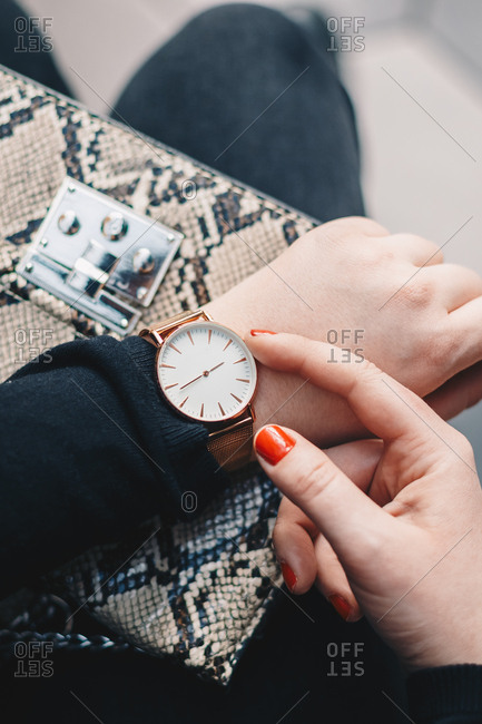 Close up detail of female fingers setting the correct time on a wrist watch, with the snakeskin handbag in the background.