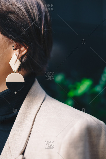 Close up detail of a strange black and white earring hanging from a brunette business woman's ear. Vertical image.