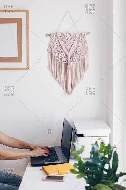 Hands using a notebook in private home office. Macrame decor hanging on the wall in the background.