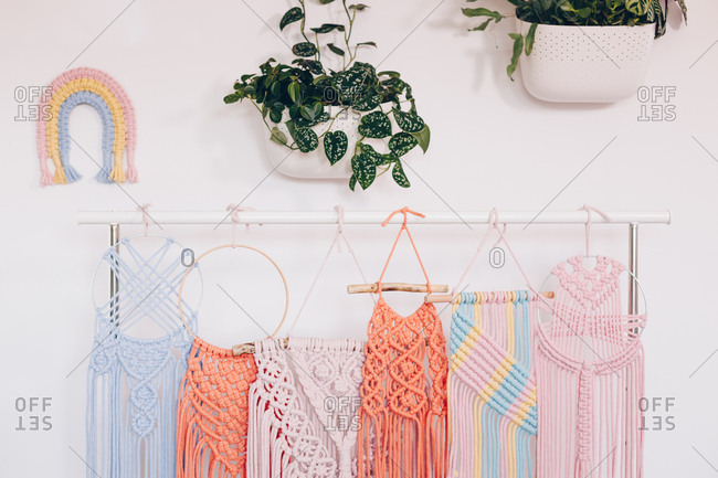 Multiple multicolored macrame's displayed on a pipe hanger in a private workshop.