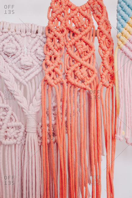 Close up of pink and red macrame threads hanging on a wall.