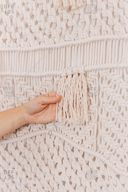 Female hands arranging a wall hanging macrame threads.