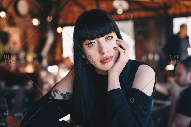 Beautiful tattooed woman sitting in a bar