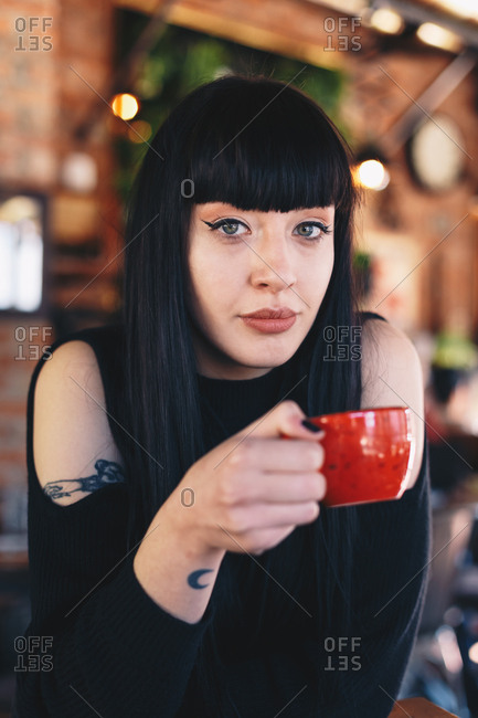 Attractive tattooed woman drinking coffee in a modern cafe bar interior.
