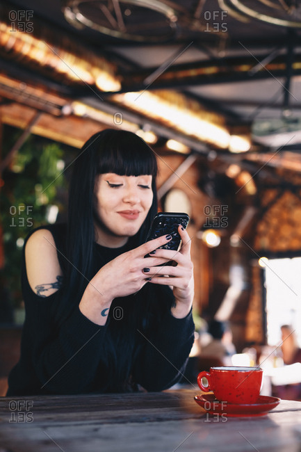 Alternative young woman browsing the internet and following social media on smartphone in a coffee bar.