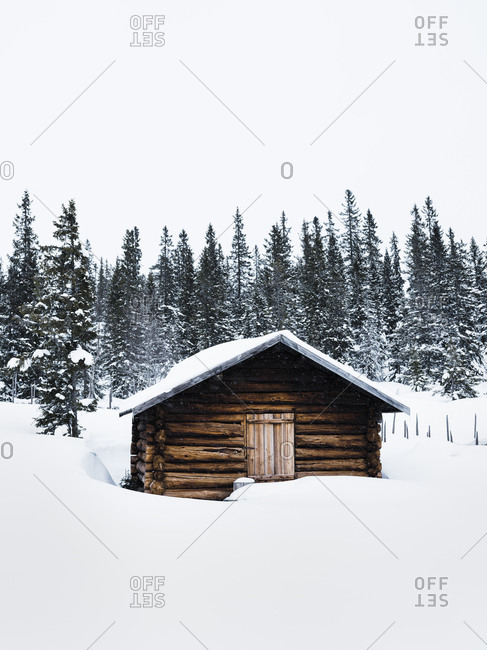 Cabin in the middle of snow covered woods