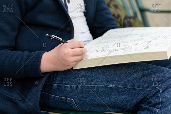 Boy drawing in a book