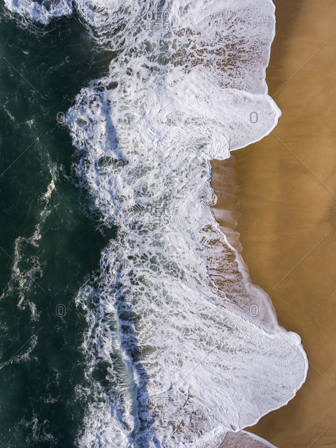 View of waves of the Atlantic Ocean washing up on the shore from above