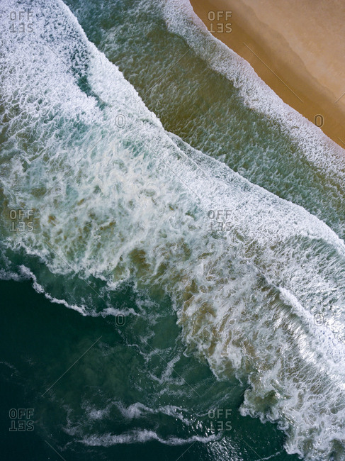 Aerial view of Atlantic Ocean waves rolling into beach