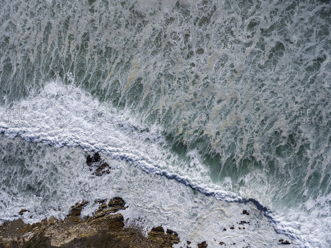 Aerial view of water in the ocean rolling into the shoreline