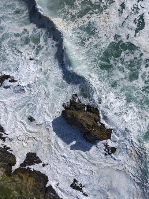 Foamy waves rolling onto rocks on the coast