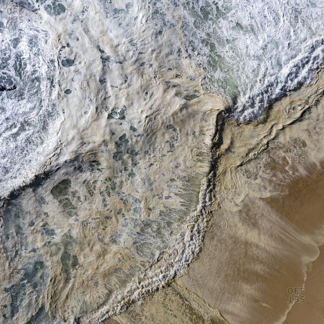 Foamy waves rolling into a sandy beach