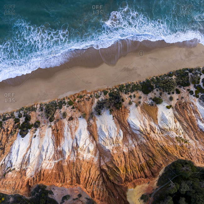 Turquoise ocean waves rolling into a beach with orange cliffs