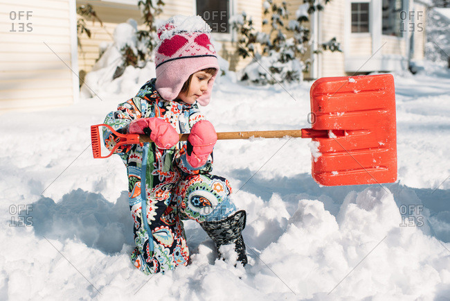 Little girl in a colorful snowsuit shoveling snow