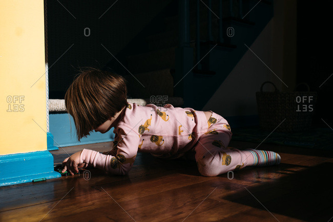 Little girl in pink pajamas playing with toy cars
