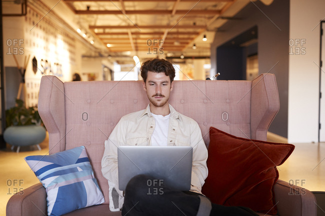 Millennial man sitting on a pink sofa using a laptop in a casual office lobby, front view