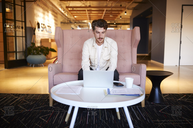 Millennial male creative sitting at a coffee table using a laptop in an office lobby, front view