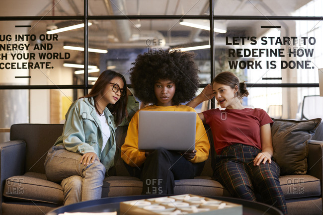 Three millennial women sitting on the sofa in an office lounge using a laptop together, front view