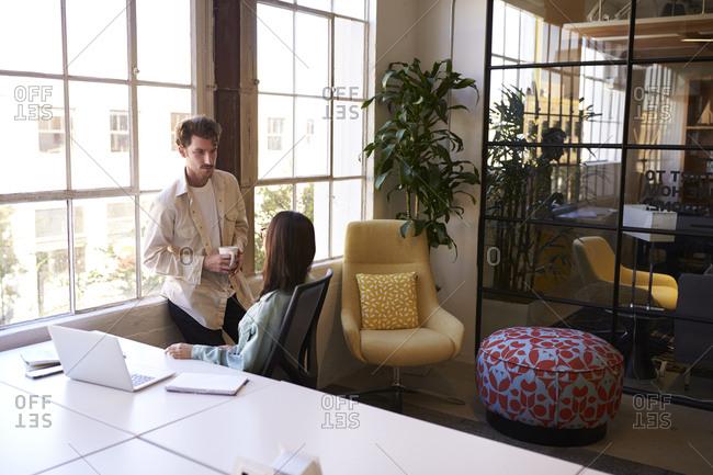 Two millennial colleagues having a coffee break, talking in a casual office