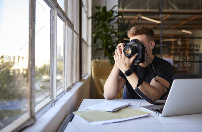 Millennial male blogger taking photos from his desk in a post-industrial office space, close up