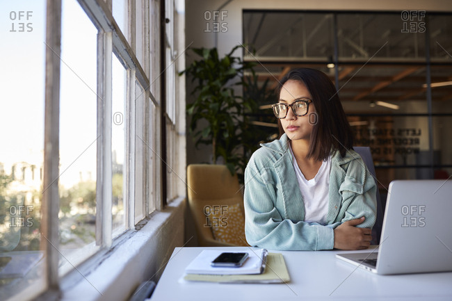 Millennial woman in glasses sitting at a desk in a casual office looking out of the window, close up