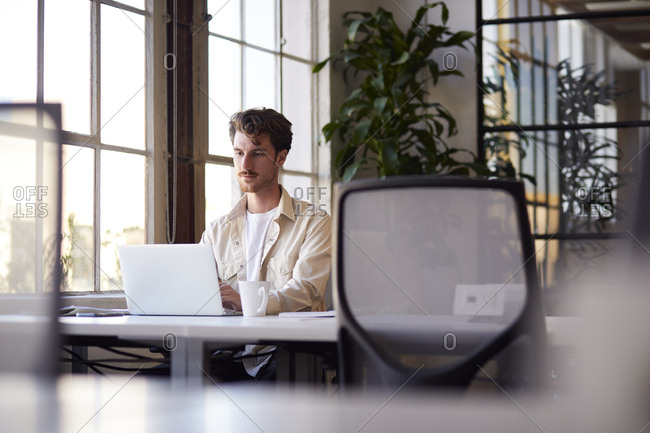 Millennial male blogger working at a desk in an office, selective focus