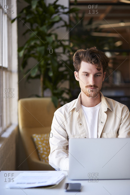 Millennial man sitting at a desk in a casual office using laptop computer, close up, vertical