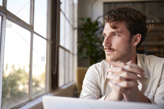 Millennial male creative sitting at a desk in an office looking out of window, front view, close up