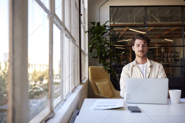 Millennial male creative sitting at a desk by the window in an office using laptop, front view