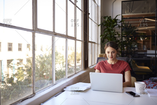 Millennial creative woman sitting by the window in a casual office using laptop computer