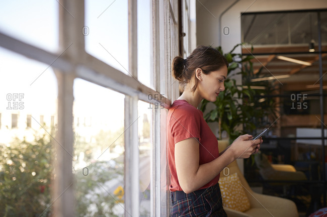 Young adult woman standing using smartphone by window in a casual creative office, close up