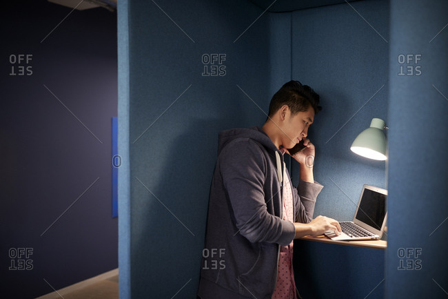Millennial man stands talking on the phone in a private booth in a casual office, side view