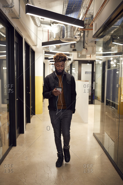 Millennial creative male walking in corridor at work using smartphone and earphones, full length