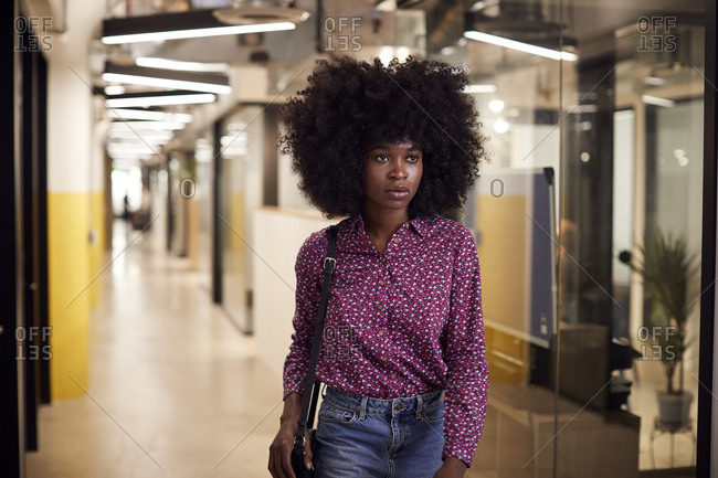Millennial female creative with afro  walking in an office corridor, close up