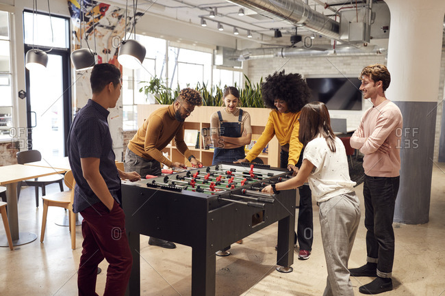 Young creative business team take a break playing table football in their office