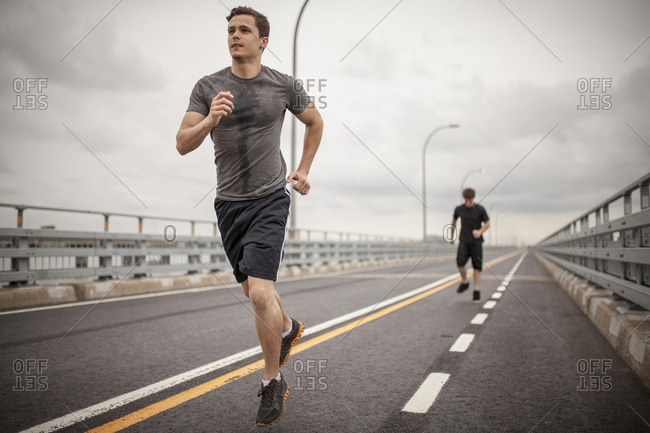 Two male athletes running together on overcast day, Montreal, Quebec, Canada
