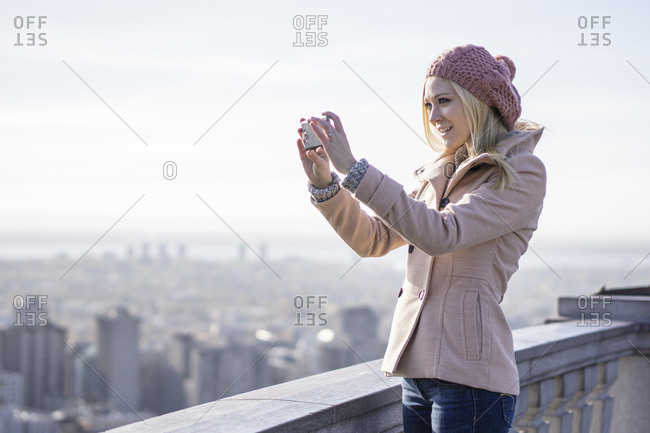 Young blonde woman using smartphone to communicate to the world, Montreal, Quebec, Canada