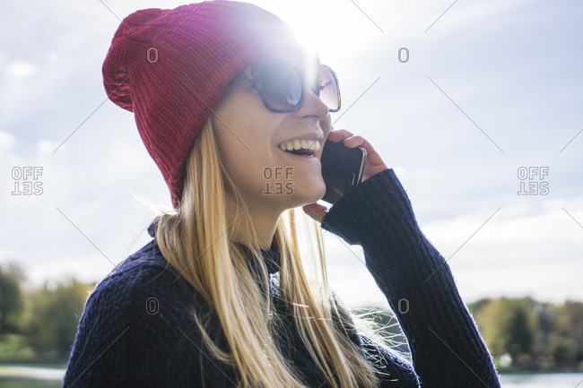 Young blonde woman in park making a phone call with happy expression, Montreal, Quebec, Canada