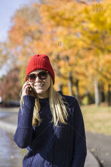 Young blonde woman in park making a phone call, Montreal, Quebec, Canada