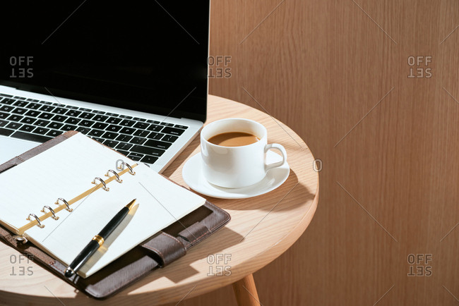 Wooden table with notebook, pen, laptop and cup of coffee