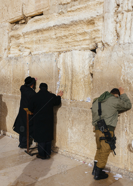 January 13, 2019: Orthodox men and soldier with gun praying at the wailing wall known also as the western wall in the old city, Jerusalem, Israel.