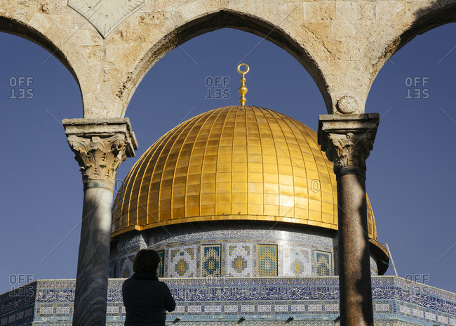 Person standing in front of the Dome of the Rock mosque, in the Temple Mount at the old city, Jerusalem, Israel.